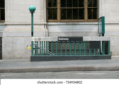 Entrance to a New York City subway station on the street in front of an old Neoclassical building. Iconic green lights marks the entrance to the train station in lower Manhattan. No people.