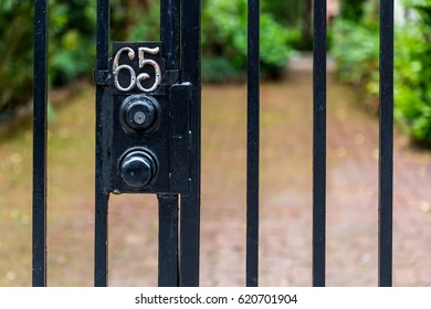Entrance Number 65.  Wrought Iron bars, a gate, and a deadbolt lock protect what's behind the number sixty five.
