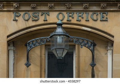 Entrance to an old Victorian Post Office with a wrought iron lantern decorated with scrolls and a frieze of flowers above the doorway