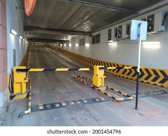 The entrance to the overground parking lot for cars with a barrier and a speed bump.