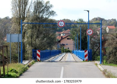 Entrance to partially renovated wavey old wooden bridge with new blue metal frame on each side and strong support with LED street lights surrounded with large dense trees and family houses in back