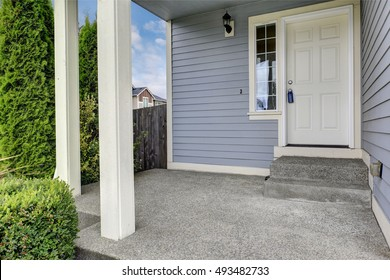 Entrance porch with concrete floor and square columns. Exterior of large blue house. Northwest, USA