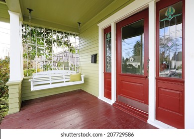Entrance porch in old house with contrast green and red walls. View of white wooden hanging swing