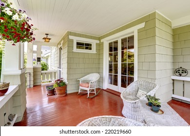 Entrance porch in old house with wicker chairs and glass entrance door. Porch decorated with flower pots