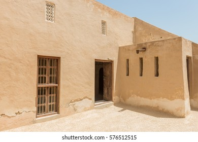 Entrance to rooms on the roof of a restored fort in the Arabian Gulf in strong sunlight. There are wooden doors and windows and carved gypsum lattices for ventilation.
