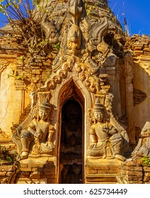 The entrance of the ruined pagoda with statues on both sides with blur view of statues inside,  in the Shwe Inn Thein monastery, Inle town, Myanmar