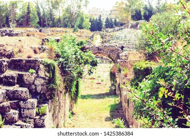 Entrance to ruins of the Roman amphitheater of Syracuse (Siracusa) – ruins in Archeological park, Sicily, Italy