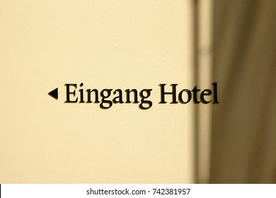 The entrance sign of a hotel on a yellow plaster facade with directional arrow / Hotel entrance direction sign