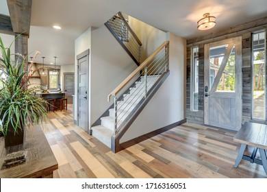 Entrada con escalera y puerta delantera, puerta rústica de madera y suelo de madera clara