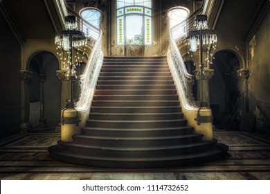 Entrance with symmetrical stairs of an abandoned casino. Sunlight shines through the windows and lights the darkness.