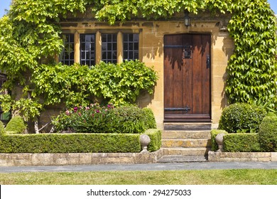 Entrance to traditional English honey golden brown stoned cottage, with wooden door surrounded by green vine, front garden with pink peony flowers, box hedge, stone ornaments by stairs, on summer day