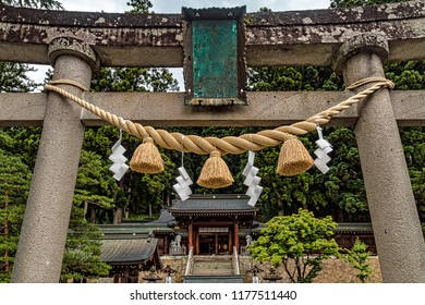 Entrance to Traditional Japanese Temple with Torii Gate and Shimenawa Rope. Temple in Nature Setting (Takayama, Japan). Summer Day, No People.