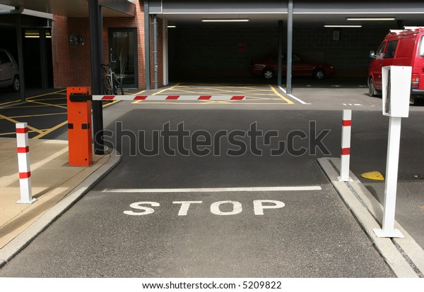 Entrance to an underground car park with gated barrier and entry machine.