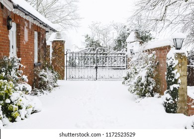 Entrance to Victorian house with cast iron gates with driveway covered in snow in winter