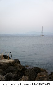 Entrance to the water from the stones on the background of the yacht in the sunset haze