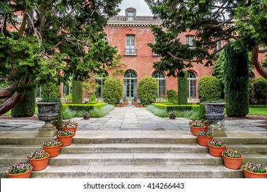 Entranceway from an old English style garden to the side entrance of a 20th century mansion. The brick walkway is lined by potted plants with flowers, rounded hedges, and other lush vegetation.