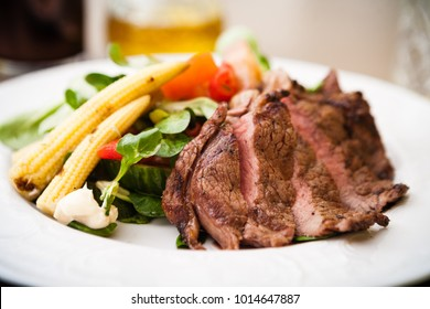 Entrecote with green salad and vegetables served on a white plate
