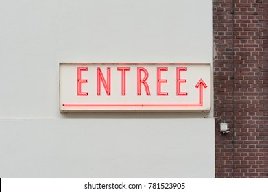 Entree word which means entrance in french neon red letters on a white wall