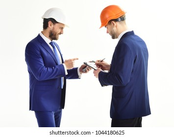 Entrepreneur and architect look confident. Business partners look at plan. Architects discuss project. Entrepreneur and architect with plans and smartphone. Construction, engineering, finance concept.