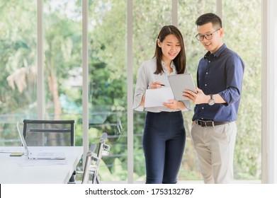 Unternehmer, asiatische Geschäftsfrau, die über neue Geschäftsprojekte diskutiert, in Tablette im modernen Sitzungssaal