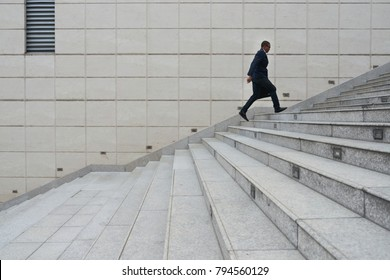 Entrepreneur with briefcase running up the stairs as he is late
