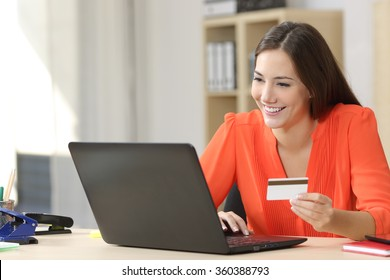 Entrepreneur buying online with a credit card and a laptop in a desk at home or a little office
