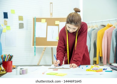 Entrepreneur fashion designer in textile business designing new retail clothing collection. Happy working woman seamstress , designer enjoy working on fabric sketches. Young designer fashion concept