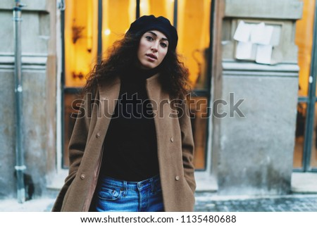 Entrepreneur female with long dark curly hair wearing light brown coat and black beret looking at the camera while standing beside old building with a wide window with warm light in the evening.
