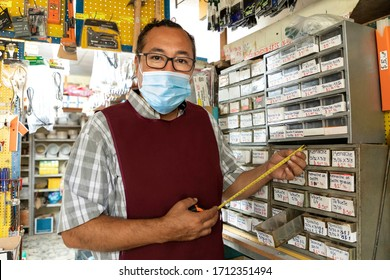 Entrepreneur in his business working with face masks during quarantine for the epidemic of disease caused by COVID-19.