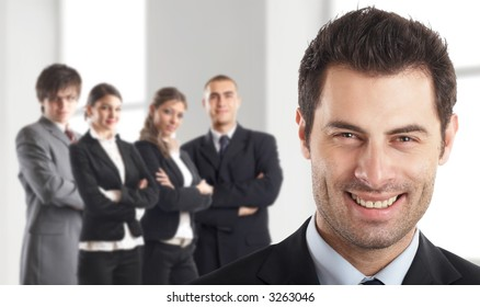 Entrepreneur - with his team behind him in an office environment - people in the background are out of focus - check my gallery for more pictures