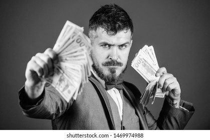 An entrepreneur or investor. Business startup loan. Rich businessman with us dollar banknotes. Currency broker with bundle of money. Bearded man holding cash money. Making money with his own business.