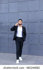 Entrepreneur man male looking at camera and smiling talks on mobile smart phone. Young handsome businessman arab muslims in business center wearing dressed in black elegant suit on building background