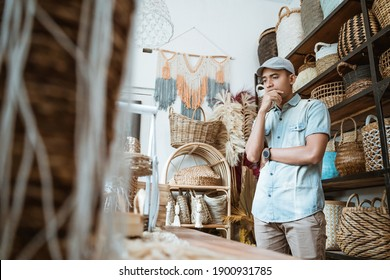 entrepreneur man with a thoughtful gesture while standing in a craft shop