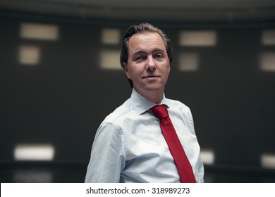 Entrepreneur with red tie in empty room.