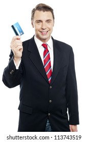 An entrepreneur showing debit card to camera isolated against white background