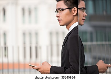 Entrepreneur with smartphone standing at mirror wall