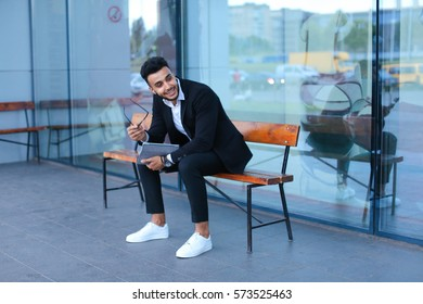 Entrepreneur smiling man  puts on sunglasses uses tablet and looks at. Young handsome businessman arab muslims in business center wearing dressed in black elegant suit on building background.