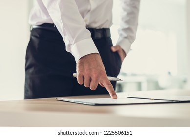 Entrepreneur standing at his office desk holding an ink pen pointing to a document or subscription form to a signature line.
