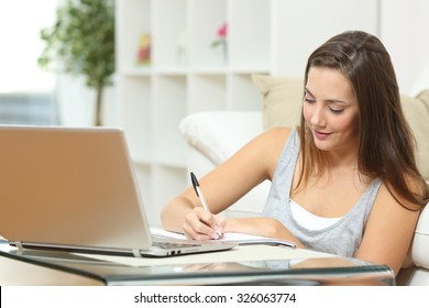 Entrepreneur or student working or studying at home and writing notes sitting on the floor at home
