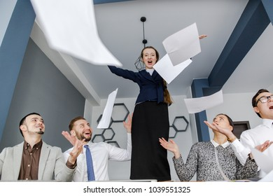 Entrepreneur throwing paper in the office standing on the table