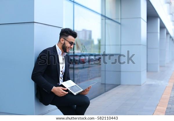 Entrepreneur uses  laptop wearing sunglasses. Young handsome businessman arab muslims in business center wearing dressed in black elegant suit on building background.