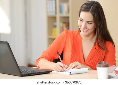 Entrepreneur working online with a laptop and taking notes in a notebook in a little office desktop or home