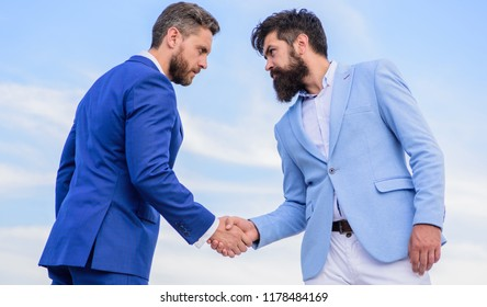Entrepreneurs shaking hands symbol successful deal. Business partner confirming deal transaction. Men formal suits shaking hands blue sky background. Business deal approved accepted by both partners.
