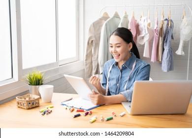 Unternehmerinnen Kleinunternehmer, asiatische Modedesignerin, die neue Skizzensammlung entworfen hat, eine Business-E-Mail an den Kunden geschickt.Verkaufserfolg,Arbeit mit Laptop,digitales Smartphone in der Werkstatt