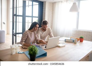 Entrepreneurs using laptop. Couple of entrepreneurs using laptop while reading e-mail from investor