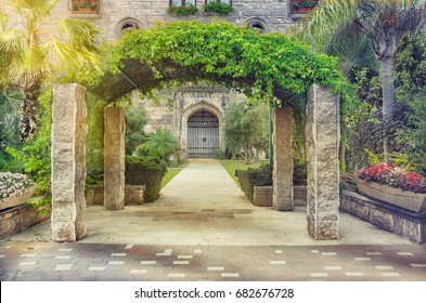 Entry arch on four columns covered by climbing plants is located in front of stone house. On either side of the wide pathway that leads to closed arched door stand green palms shrubs and flower beds