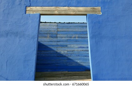 Entry in a blue facade with a wooden wall blocking the view
