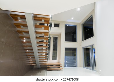 Entry in contemporary mansion with wooden staircase