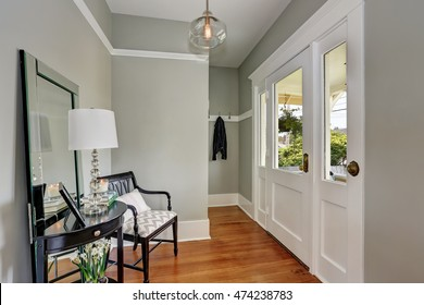 Entryway with gray walls, console table with mirror and wood floors. Northwest, USA
