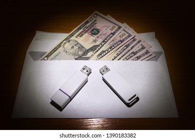 Envelope with an American Dollars and Two USB Drives on the Table in the Dark